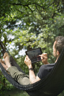 Relaxed man lying in hammock with digital tablet - ONF000829