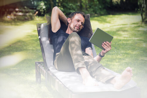 Relaxed man lying in sun lounger in garden using digital tablet - ONF000835