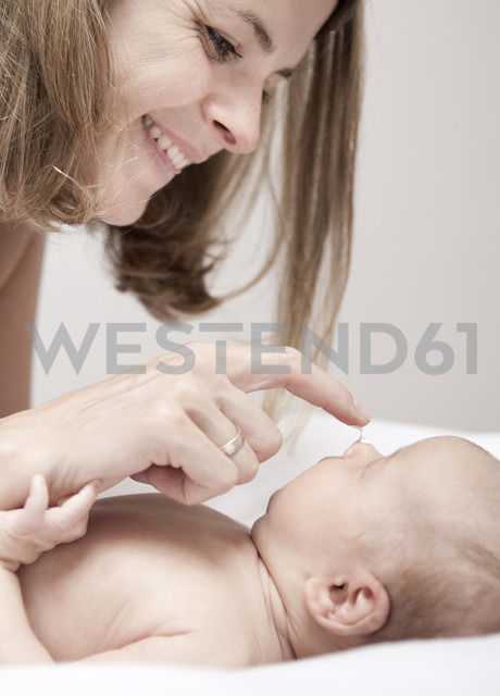 Young woman creaming baby lying on changing table - MFRF000292