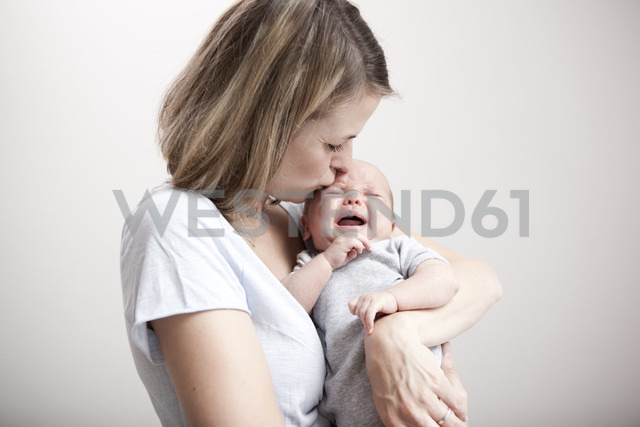 Young woman kissing crying baby - MFRF000295