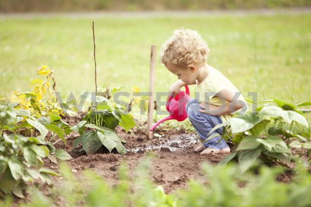 Little girl crouching in the garden watering plants - MFRF000321