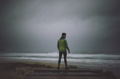 Spain, Valdovino, rear view of jogger standing at the ocean on a stormy day - RAEF000270