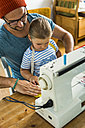 Father and daughter at home using sewing machine - UUF005130