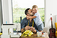 Happy daughter cuddling father at home - UUF005145