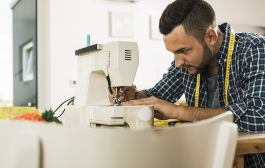 Young man at home using sewing machine - UUF005147