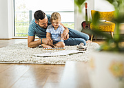 Father with daughter on rug playing glockenspiel - UUF005152