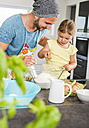 Father and daughter baking in kitchen - UUF005165