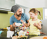 Father and daughter baking in kitchen - UUF005171