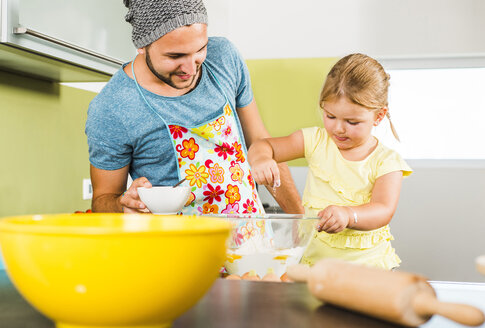 Father and daughter baking in kitchen - UUF005210