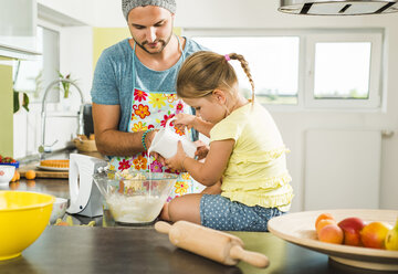 Father and daughter baking in kitchen - UUF005172
