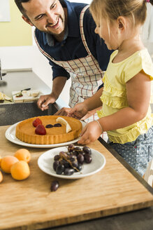 Happy father and daughter in kitchen preparing fruit cake - UUF005182
