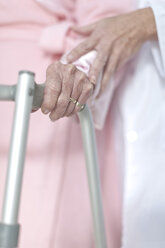 Elderly patient with walking frame being supported - ZEF007238