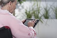 Elderly patient in wheelchair using digital tablet - ZEF007243