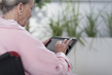 Elderly patient in wheelchair using digital tablet - ZEF007243