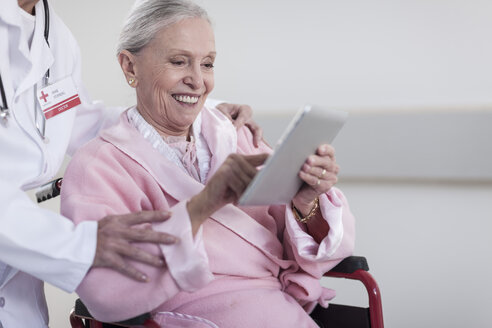 Smiling elderly patient in wheelchair using digital tablet - ZEF007247