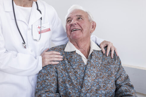 Doctor and smiling elderly patient in wheelchair - ZEF007250
