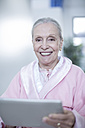Smiling elderly woman in hospital corridor with digital tablet - ZEF007267