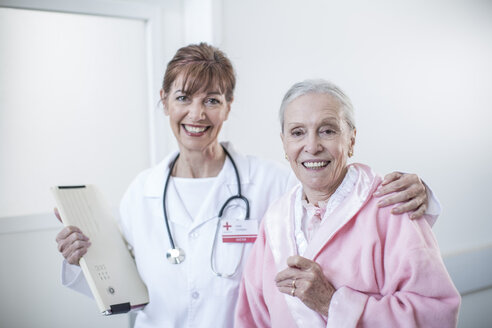 Portrait of doctor and smiling elderly patient in hospital - ZEF007256