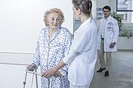 Nurse leading elderly patient with walking frame on hospital floor - ZEF007271