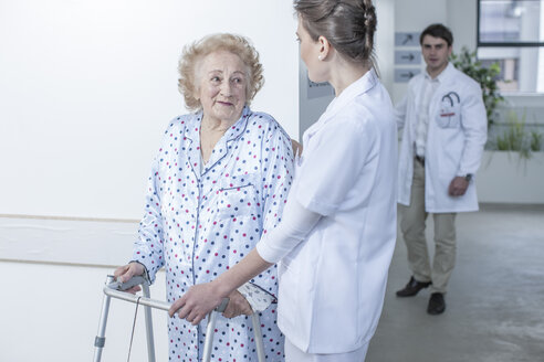 Nurse leading elderly patient with walking frame on hospital floor - ZEF007271