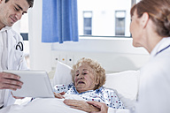 Doctor showing digital tablet to elderly patient in hospital bed - ZEF007278