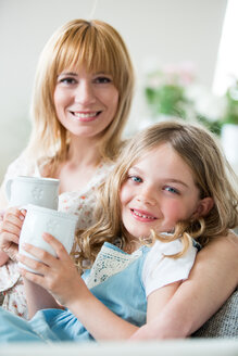 Mother ans daughter sitting on couch with drinking cups - WESTF021491