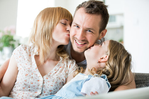 Happy family sitting on couch, mother and daughter kissing father - WESTF021497