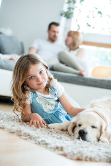 Little girl cuddling with her dog, lying on floor, parents in background - WESTF021548