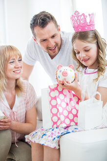 Girl wearing pink crown holding gift bags, parents watching - WESTF021563