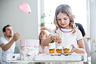 Girl garnishing cup cakes, familiy celebrating in background - WESTF021569