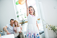 Girl playing with balloons, parents watching - WESTF021575