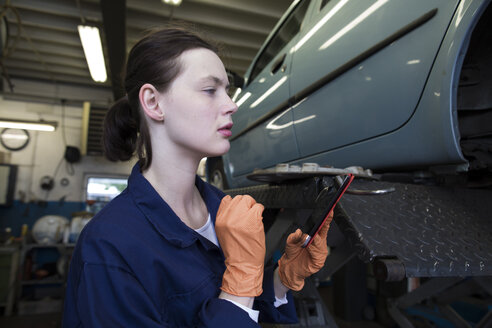 Young woman in repair garage checking data with digital tablet - SGF001804