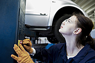 Young woman working in repair garage, pressing hoist button - SGF001806