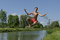 Germany, Bavaria, teenage boy jumping into River Loisach - LBF001161