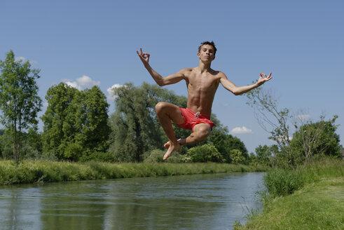 Germany, Bavaria, teenage boy jumping into River Loisach - LBF001161