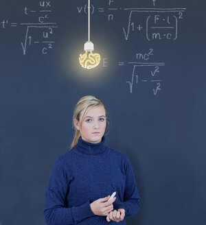 Schoolgirl in front of blackboard with formula - KLRF000083