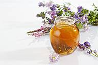 Glass of blossom honey with honeycomb and blossoms on white ground - CSF025977