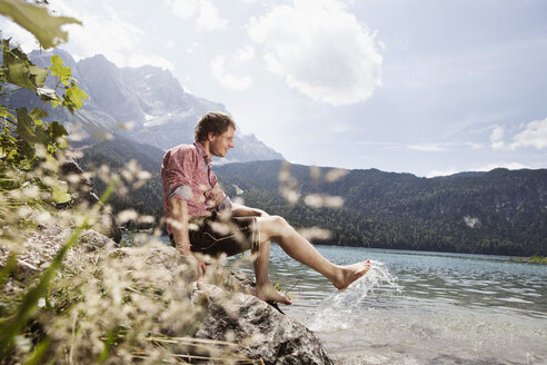 Germany, Bavaria, Eibsee, smiling man in lederhosen splashing in water - RBF003006