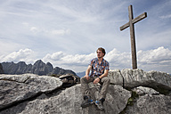 Germany, Bavaria, Osterfelderkopf, man sitting at summit cross - RBF003012