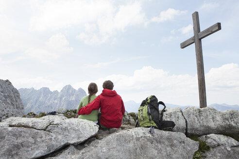 Germany, Bavaria, Osterfelderkopf, couple resting at summit cross - RBF003018