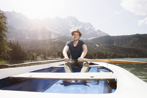 Germany, Bavaria, Eibsee, man in rowing boat on the lake - RBF003033