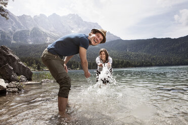 Germany, Bavaria, Eibsee, playful couple splashing in water - RBF003044