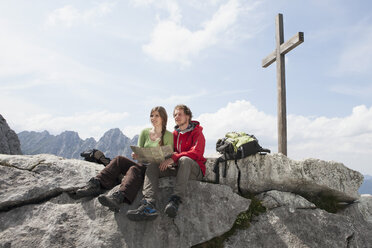 Germany, Bavaria, Osterfelderkopf, couple with map resting at summit cross - RBF003049