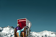 Austria, Altenmarkt-Zauchensee, skier sitting in hooded beach chair in the mountains - HHF005358