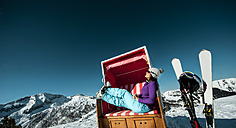 Austria, Altenmarkt-Zauchensee, skier sitting in hooded beach chair in the mountains - HHF005362