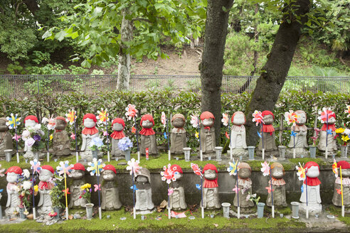 Japan, Tokyo, rows of Jizo statues decorated with bibs, knitted caps, flowers and pinwheels at Zojoji temple - FL001217