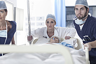Doctors pushing a bed with patient - ZEF007335