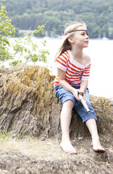 Girl dressed up as pirate sitting on a rock - MFRF000286