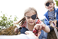 Boy and girl dressed up as pirates receiving cherries - MFRF000289