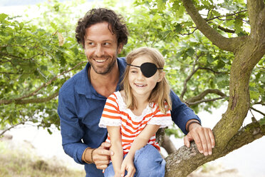 Father with daughter dressed up as pirate sitting on a tree - MFRF000281